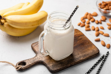 Aluminium Prints Milkshake Banana protein smoothie in drinking glass on wooden serving board. Closeup view