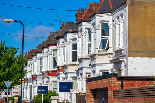 A row of typical British terraced houses in London with estate agent boards