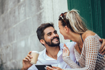 Romantic tourist couple sitting on stairs and drinking coffee, using digital tablet.