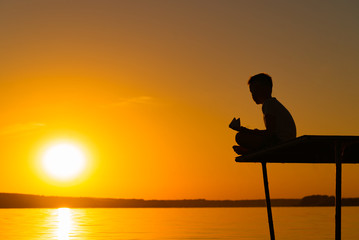 a small child sits on a bridge in a lotus pose and holds a paper ship at sunset. A kid plays with origami over the river
