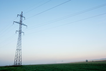 Supports high-voltage power lines against the blue sky on sunrise. Electrical industry.