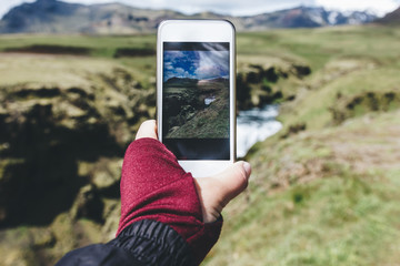 cropped image of woman taking picture of landscape with Skoga river on smartphone in Iceland