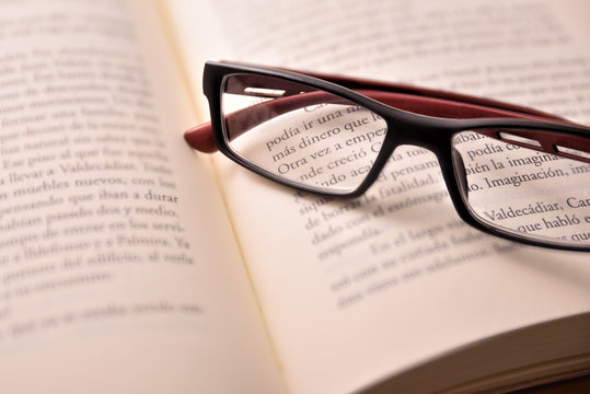 Black and red reading glasses on open book