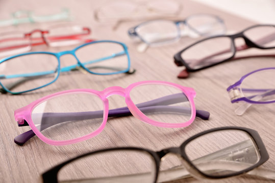 Assortment of glasses on wooden table in an eyewear store