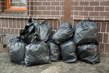 Pile of black trash bags filled with garbage near brick wall on the street