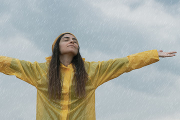Woman wearing yellow raincoat out in the rain