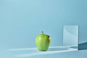 The apple is green, a square mirror on a blue background, a reflection of an apple and from shadows in a mirror.