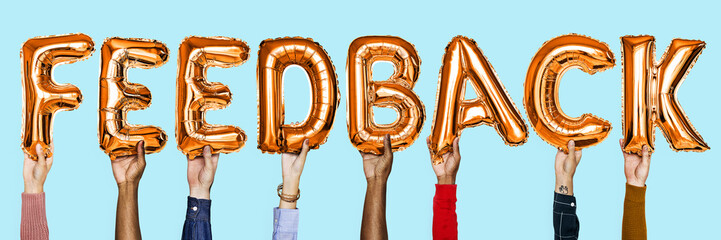 Orange alphabet helium balloons forming the text feedback