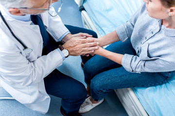 overhead view of mature male doctor holding hands of female patient in hospital room