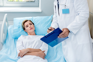 partial view of male doctor with stethoscope over neck pointing at clipboard to female patient in hospital room