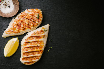 Grilled chicken breast served on black slate Wall mural