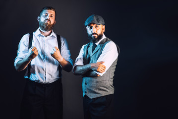 Two bearded men in vintage suits like a gangsters angry looking on the black background
