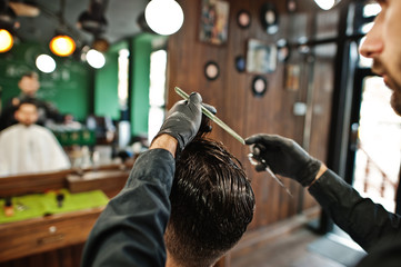 Handsome bearded man at the barbershop, barber at work.