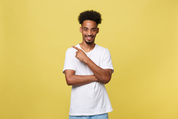 Young handsome african american man over yellow background pointing upwards.