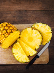 Pineapple on wood texture background. Whole and sliced tropical pineapple on wooden cutting board  with copy space. Flat lay