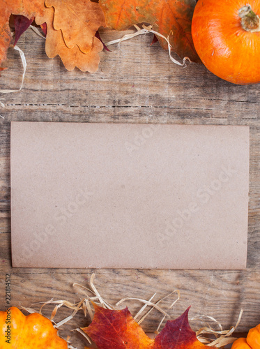 Thanksgiving Day Card With Orange Pumpkins And Colourful Leaves On Wooden Background With Blank Tag Paper