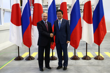 Russian President Putin shakes hands with Japanese PM Abe during their visit to the Mazda Sollers Manufacturing Rus joint venture plant of Sollers and Japanese Mazda in Vladivostok