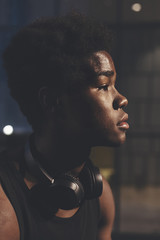 Side view headshot of  young confident afro man wearing black headphones in urban scenery at dusk