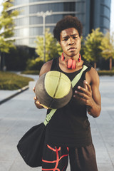 Portrait of young afro man with a basket ball, wearing red headphones and a bag waiting friends in urban scenery