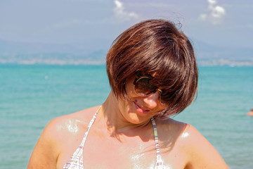 portrait of a girl wearing glasses on the beach.
