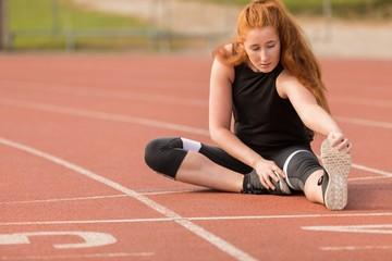 Female athletic exercising on running track