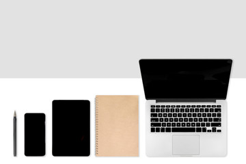 Flat lay photo of office table with laptop computer, digital tablet, mobile phone and accessories. on modern two tone (white and grey) background. Desktop office mockup concept.