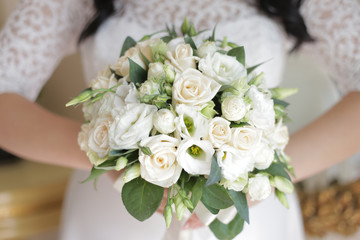 the bride is holding a bouquet of the bride from white roses and eustoma
