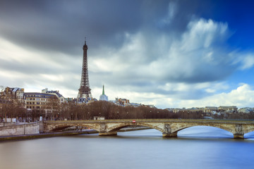 Beautiful long exposure view of the river Seine in Paris, with the Eiffel tower in the background, on a cloudy winter day