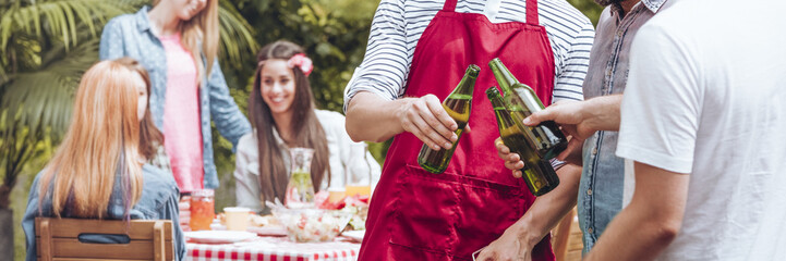 Cropped photo of three friends holding bottles of beer and girls talking in the background during a grill party