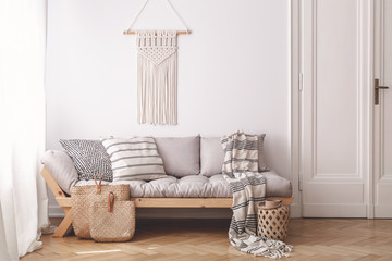 Beige wooden sofa and bags in white loft interior with decor on the wall next to door. Real photo