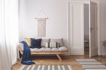 Blue blanket and pillows on wooden couch in white living room interior with rugs and door. Real photo