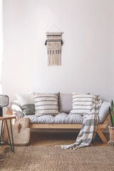 Blanket and cushions on wooden couch in beige living room interior with brown carpet. Real photo