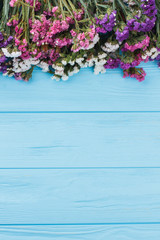 Multicolored limonium flowers on wood. Free space for text, copyspace.