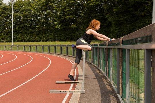 Female athlete exercising on railing at sports track