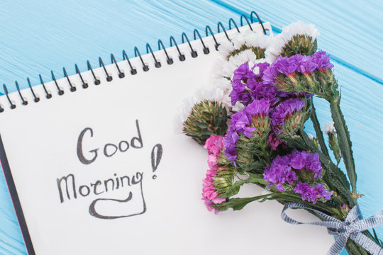 Good morning wish concept. Bouquet of statice limonium flowers and notepad with good morning wish. Blue background.