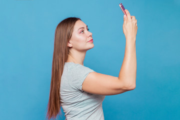Young caucasian woman with brown hair and light blue eyes making selfie. Blue background, studio, isolated