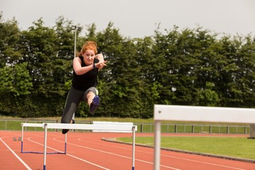 Female athletic jumping over hurdle on sports track