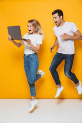 Excited young loving couple jumping isolated over yellow wall background using laptop computer.