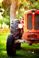Wall Mural - An old vintage red tractor standing on a farm field at sunset