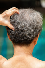 Senior woman scratching back head, thinking about something, Grey curly hair, Close up, Body concept