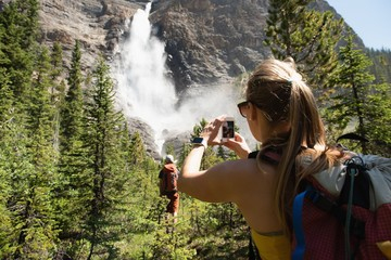 Female hiker clicking pictures with mobile phone
