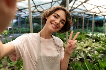 Cute woman gardener standing over plants in greenhouse take a selfie by camera with peace gesture.