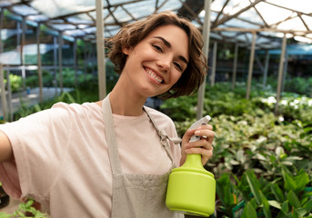Woman gardener standing over plants in greenhouse take a selfie by camera.