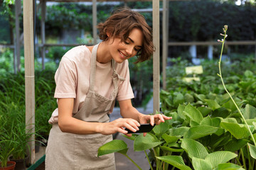Cute woman gardener working over plants in greenhouse take a selfie by mobile phone.