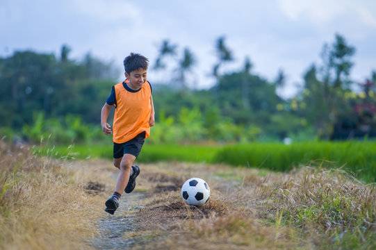 8 or 9 years old happy and excited kid playing football outdoors in garden wearing training vest running and kicking soccer ball