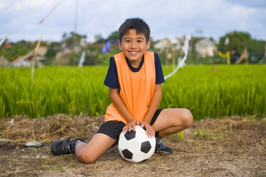 lifestyle portrait of handsome and happy young boy holding soccer ball playing football outdoors at green grass field smiling cheerful wearing training vest