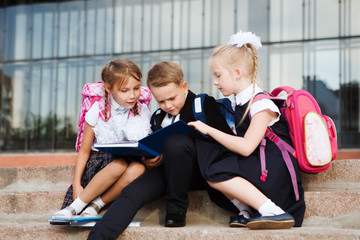 Group of little school kids  reading book outdoor