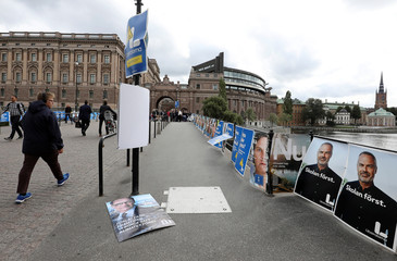 People walk past election posters near the Swedish parliament in Stockholm