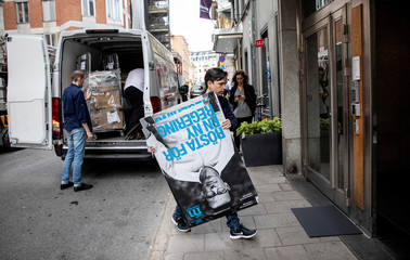 Election workers unload posters with a portrait of Moderate Party leader Ulf Kristersson outside the party headquarters in central Stockholm