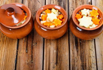 Traditional rustic home vegetable stew in three clay pots on old vintage wooden table.